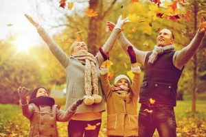 Miami Home Inspectors a family throwing leaves and enjoying the autumn season