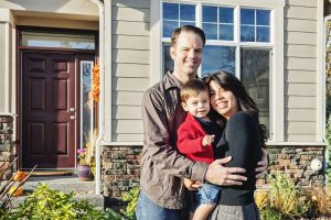 Miami Home Inspectors couple with their son standing in front of their house