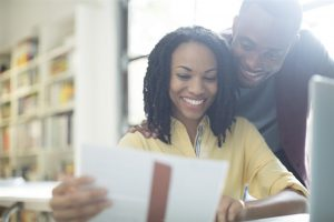 happy couple  looking at a piece of paper - home inspection miami
