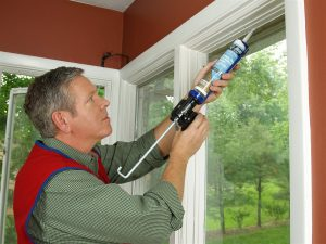 man sealing a window - home inspection miami